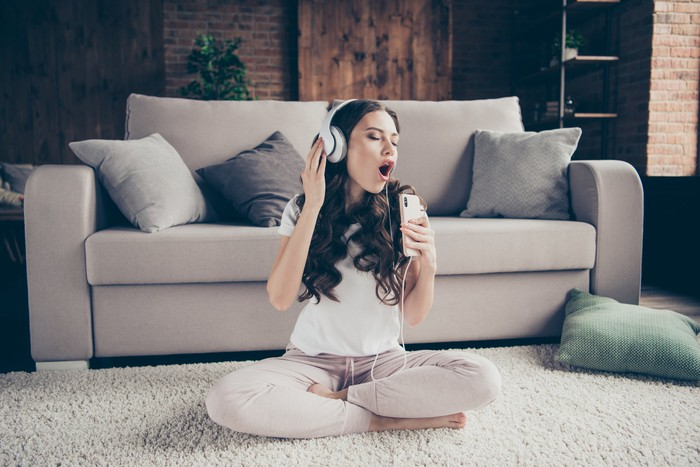 Girl sitting on the floor in front of a couch while wearing headphones and singing into her phone