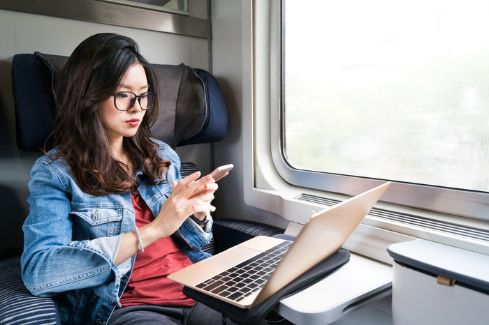 Young woman using smartphone and laptop on a train.