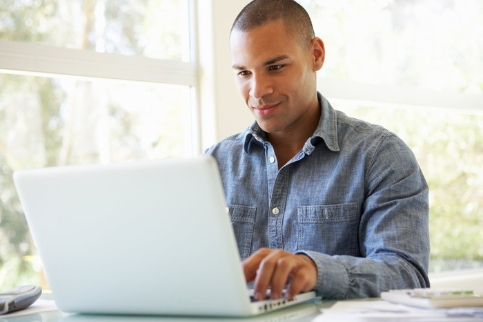 Smiling young male adult at laptop