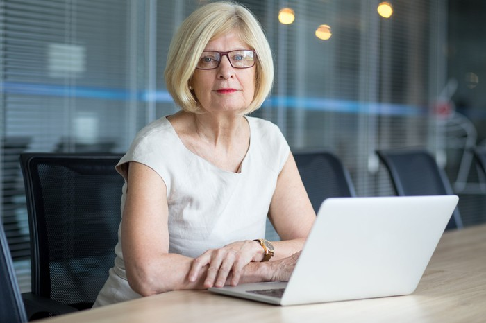 A female executive sitting at a conference room table with her laptop in front of her.