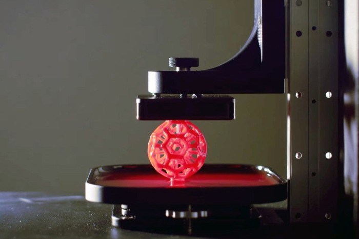 A red lattice-like ball rising from a pool of liquid as it's printed using Carbon's 3D printing tech.
