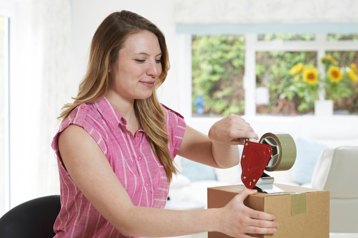 A woman puts tape on a box.
