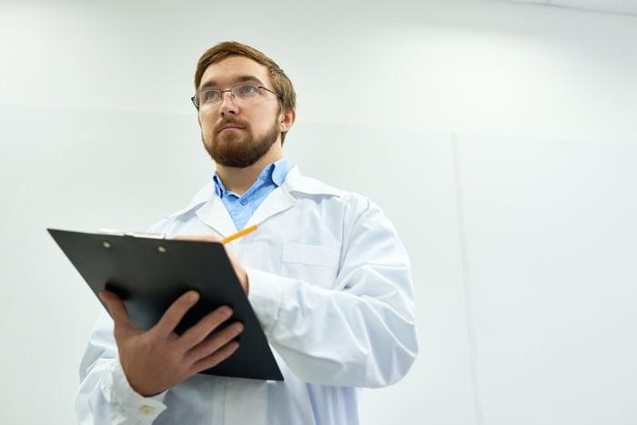 Guy in a lab coat keeping score on a clipboard.