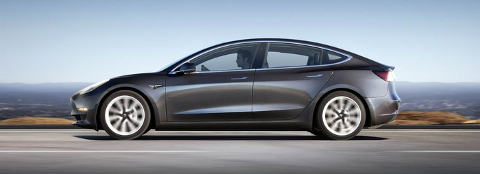 A Tesla Model 3 viewed from the side.