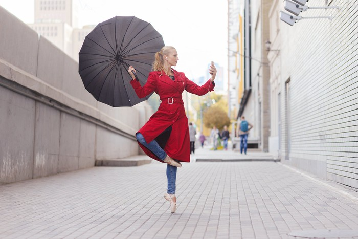 A young woman records herself dancing with an umbrella.