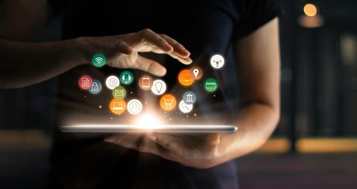 A digital depiction of mobile apps hovering above a tablet.