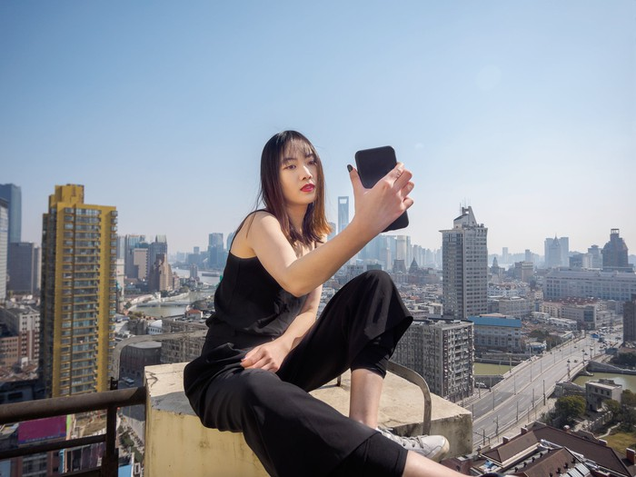 A young woman taking a selfie on top of a building.
