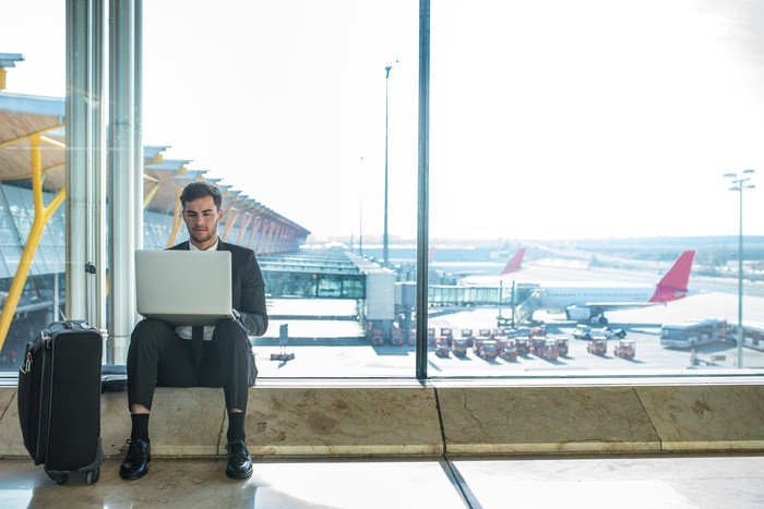 A business traveler uses a laptop at the airport.