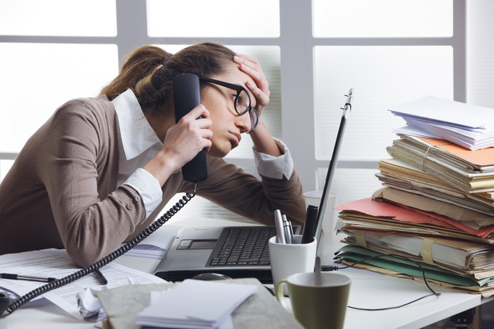 Woman on phone at cluttered desk holding her head as if bored