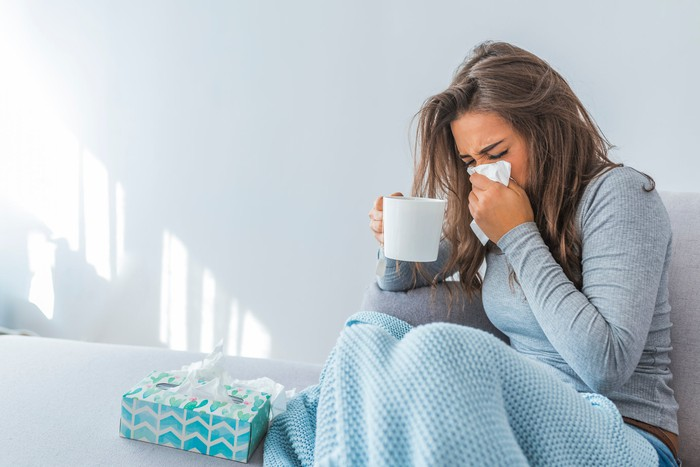 Woman sitting under a blanket on a bed and holding mug in one hand and blowing nose with other hand, with a box of tissues by her side.