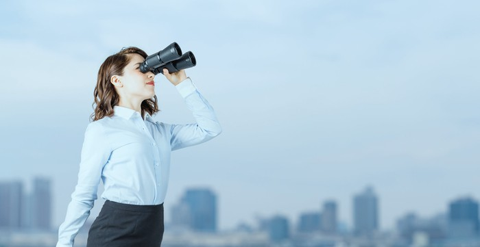 A woman looking through binoculars.