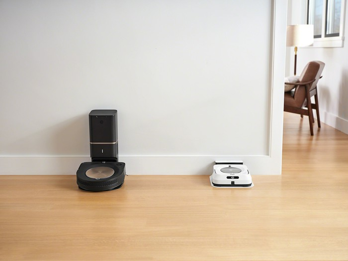 iRobot's new Roomba s9+ and Braava jet m6 docked near each other along a baseboard.