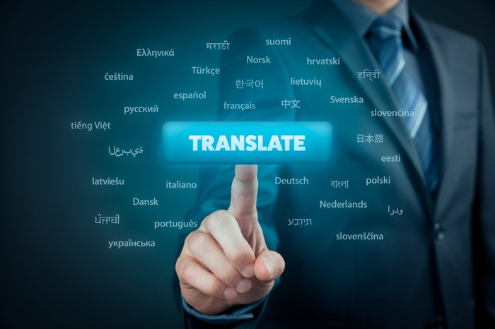 "A man in a suit reaches out and touches a virtual rectangle button with the word ""Translate"" on it with other buttons with names of languages on them all around it."