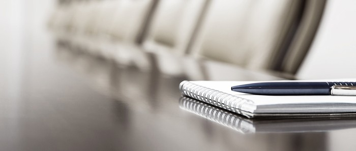 A pen on top of a notebook that's set on a long conference table.