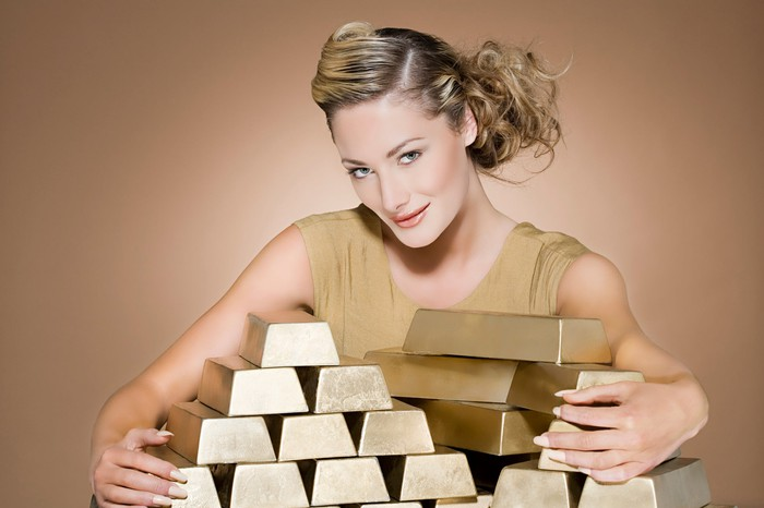 A woman wrapping her arms around stacks of gold bars