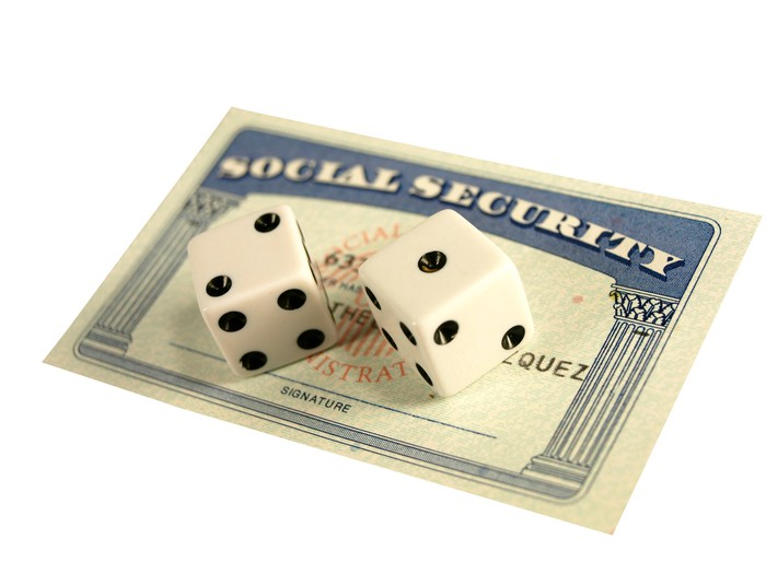 Two dice on top of a Social Security card.