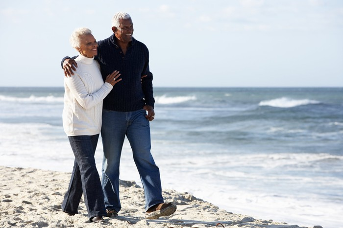 Senior man and senior woman walking on beach with arms around each other