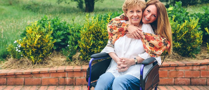 Woman putting arms around older woman sitting in wheelchair