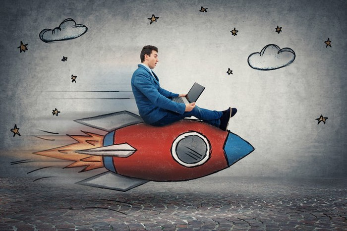 A businessman holding a computer and riding a cartoon rocket, with clouds and stars painted on a back wall.