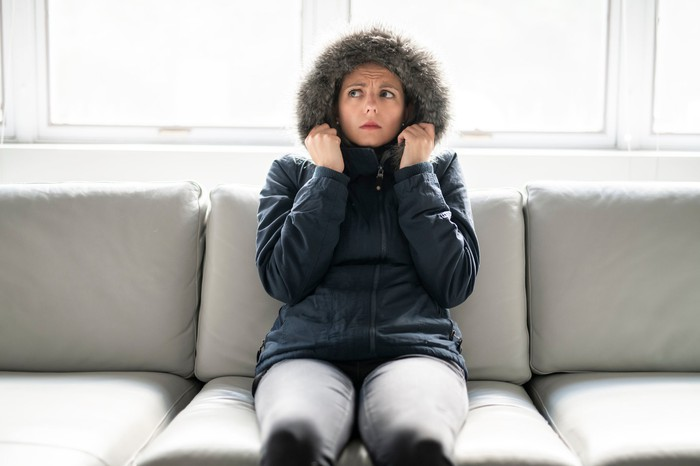 A women in a heavy coat and a worried look sits on a couch.