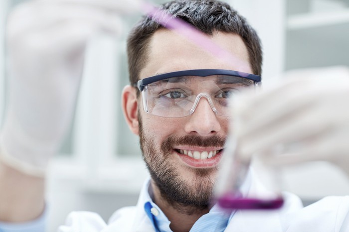 Smiling man in a lab coat using a pipette to put purple liquid into a beaker.