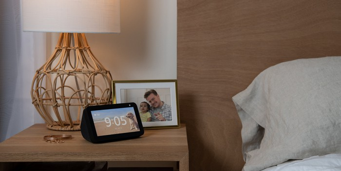 Echo Show 5 on a nightstand next to a lamp and a framed photo