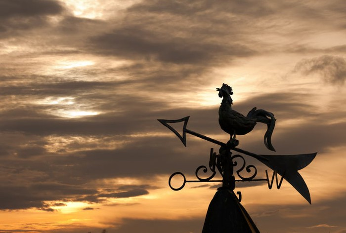 A wind vane topped with a rooster, silhouetted against a twilight sky