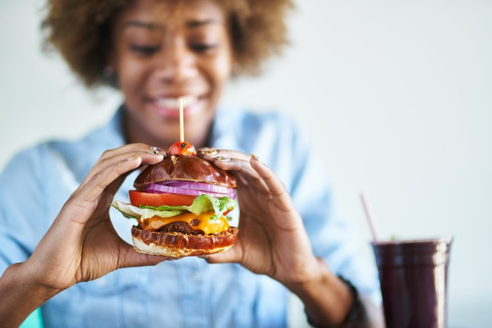Smiling woman about to eat a vegan cheeseburger