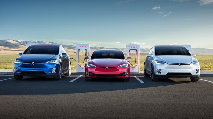 Three Tesla vehicles charging at a Supercharger location