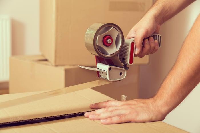 Man rolling packing tape across cardboard box