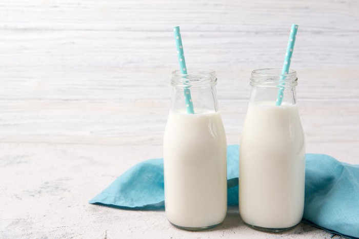 Two jars of milk with one straw in each.