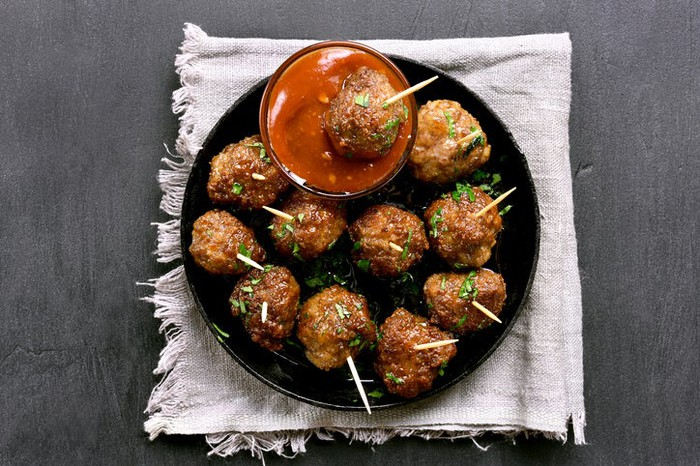 Meatballs made from cultured meat, on a platter, with dipping sauce.
