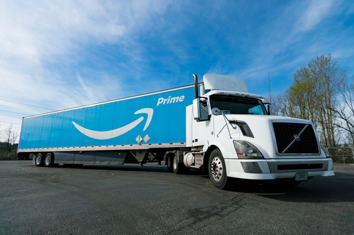 An Amazon tractor trailer on a road with a blue sky in the background.