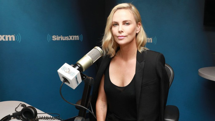 Charlize Theron sitting in front of a microphone at a Sirius XM Town Hall event
