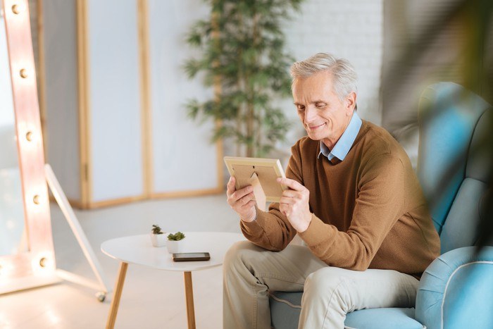 Older person looking at a framed picture.
