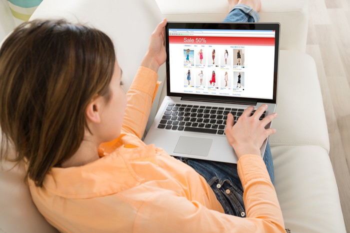 A woman sitting on a couch while shopping online with a laptop.