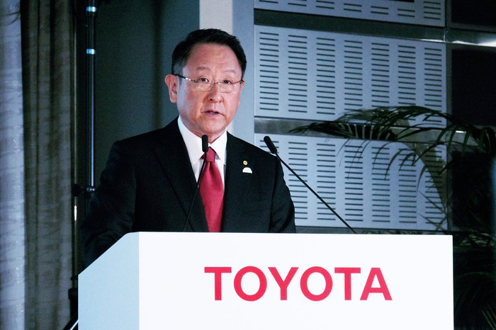 Toyota CEO Akio Toyoda, in a dark suit and red tie, speaking at a white podium with a red Toyota logo.