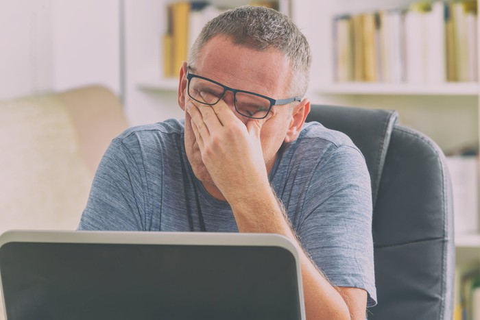 Man sitting at laptop, covering eyes as if stressed