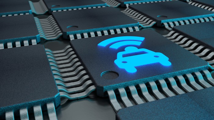 Digital rendering of several interconnected microchips, where the chip in focus features a graphic design of a car sending radio waves upward.