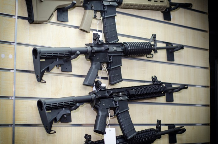 Military assault-style weapons hanging on a wall rack