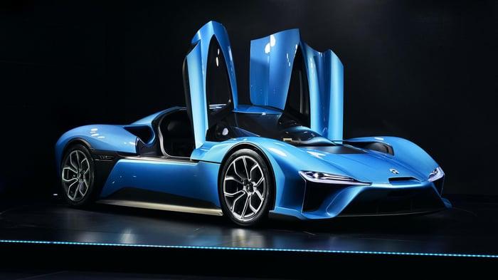 Blue sports car with doors opening upward.