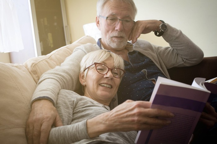 Senior couple on couch, reading a book.