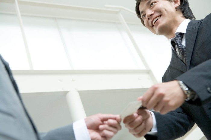Man in suit handing business card to another man in suit