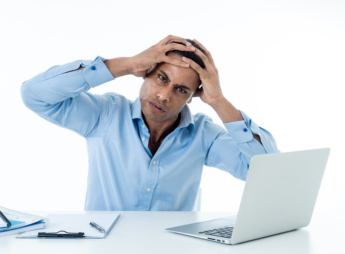 A man with a pained expression holds his hands to his head in front of a laptop.