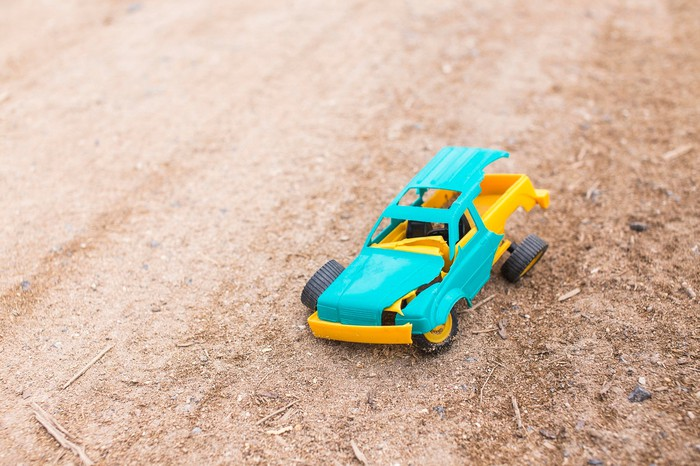 A plastic toy truck, broken and lying on the ground
