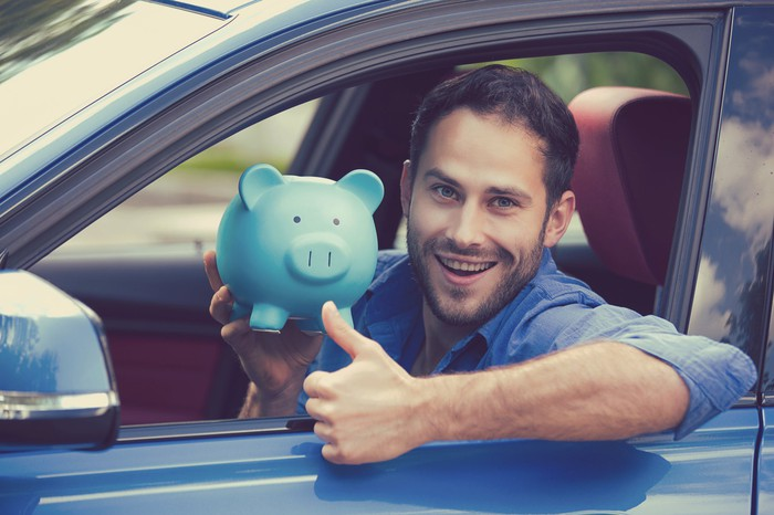 Man in a car holding a piggy bank, while giving a thumbs-up sign