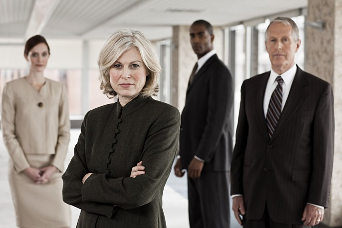 Two men and two women in business suits with serious expressions