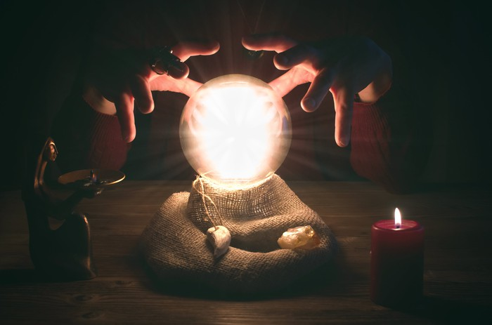 A glowing crystal ball with hands positioned above in a darkened room.