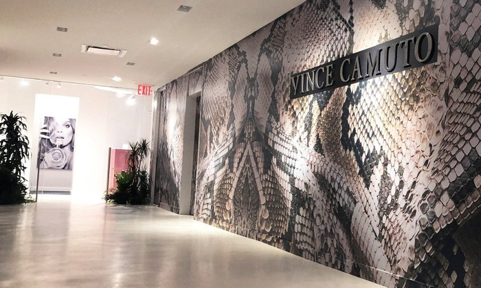 Mosaic-designed wall with Vince Camuto sign on it.