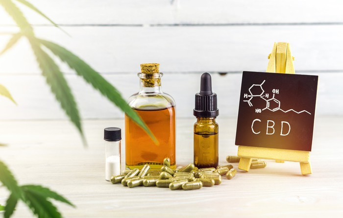 Cannabis leaves, CBD oils, CBD pills, and a small chalkboard with the chemical structure of CBD drawn on it.